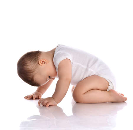 Portrait of sweet cute baby boy toddler in white body barefoot crawling on floor and looking down at legs over white background in studio, side view. Happy infancy and babyhood concept Stok Fotoğraf - 152866560