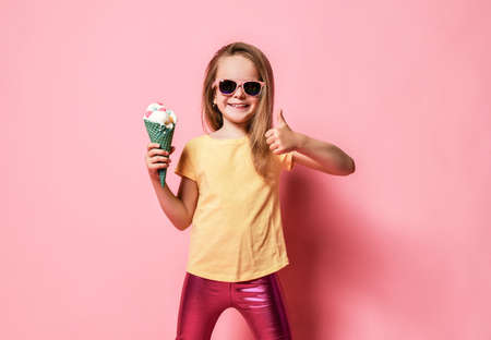 Happy smiling laughing kid girl in yellow t-shirt and glossy pink leggings holds big vanilla ice cream with candies in waffles cone and shows thumb up over pink background