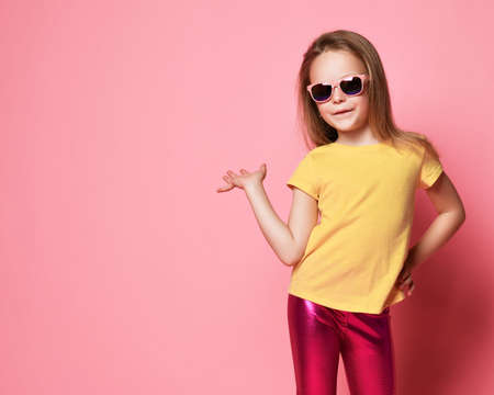 Smiling frolic kid girl in sunglasses, yellow t-shirt and leggings holds hand up with open palm as if she holds something on it over pastel pink background with free copy space