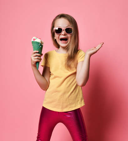 Excited happy screaming kid girl preschooler in yellow t-shirt and glossy leggings is posing with big vanilla ice cream with candies in waffles cone she holds in hand