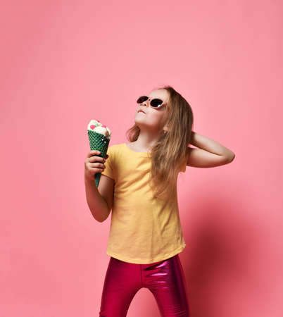 Stylish kid girl preschooler in yellow t-shirt and pink glossy leggings stands with big vanilla ice cream with candies in waffles cone looking up at free copy space