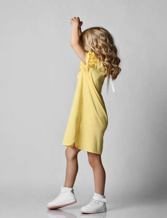 Blonde curly kid girl preschooler in yellow dress and sneakers is walking dancing spinning with her hands up over grey background, side view. Stylish casual fashion for children