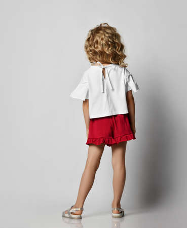 Full-growth portrait of blonde kid girl with curly hair in stylish casual clothing shorts and t-shirt standing posing back to us over grey wall background. Fashion for children concept Archivio Fotografico