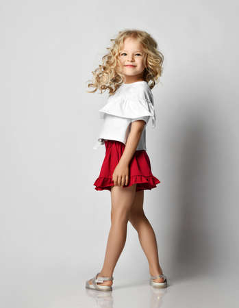 Smiling blonde kid girl with curly hair in stylish casual clothing shorts and t-shirt standing posing back turned to us over grey wall background. Fashion for children concept