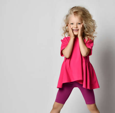 Cute smiling blonde curly kid girl in stylish casual shorts and t-shirt is posing covering cheeks with hands over gray background. Fashion for children concept Archivio Fotografico