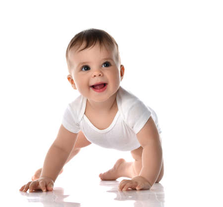 Happy laughing toddler baby in white bodysuit is crawling on floor and looking up at the corner trying to stand up on white background. Happy infancy and babyhood concept