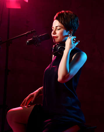 Inspired short haired brunette woman in elegant black dress sits in studio in headphones and sings in microphone over dark background. Beautiful singer concept