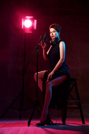 Inspired short haired brunette woman in elegant black dress and high heeled shoes sits in studio in headphones at microphone over dark background. Beautiful singer concept