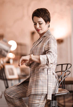 Young short haired brunette woman in elegant business plaid pantsuit sits on a high chair in room appartement office gallery and looking at her watches. Business elegance concept Stok Fotoğraf