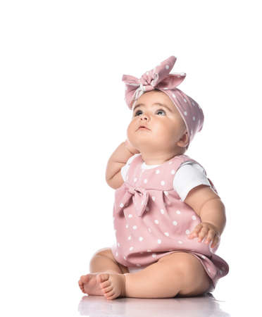 Thoughtful barefooted Infant baby toddler in polka dot dress and headband with bow sits on the floor looking up holding hand at head. Happy infancy and babyhood concept