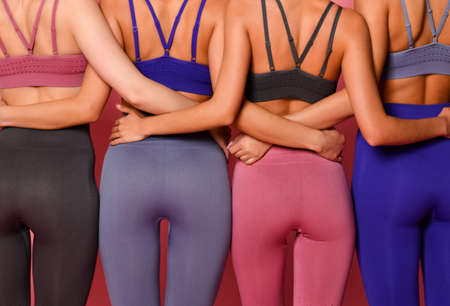Close up portrait of group of four hugging athletic women girls with perfect buttocks in blue gray and brown sport wear standing together after workout on pink background