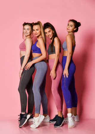 Four tall sport girls international friends on pink background. Yoga fitness instructors in blue, grey, brown training suits are standing behind each other in line