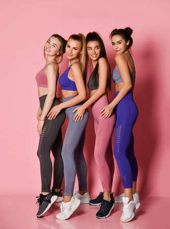 Four tall healthy sport girls friends on pink background. Yoga fitness instructors in blue, grey, brown training suits are standing behind each other in line