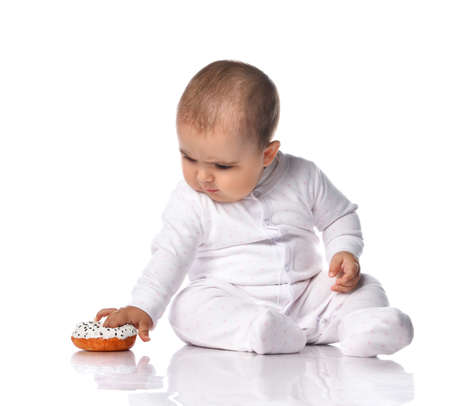Curious interested infant baby toddler in white onepiece jumpsuit overall sits on the floor and picks up, plays with a donut lying on the floor. Happy infancy and babyhood concept