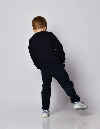 Blond kid boy in black sweater, pants and white sneakers stands back to us with his hands in pockets swaying from side to side and looks down over gray background