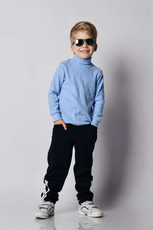 Smiling blond kid boy in sneakers, black sport pants, blue turtleneck sweater and sunglasses stands with his hands in pockets over gray background Imagens