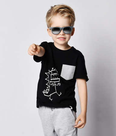 Cool blond kid boy in sunglasses, black t-shirt with dinosaur print and gray pants pointing finger at camera gesturing  over gray background Stok Fotoğraf