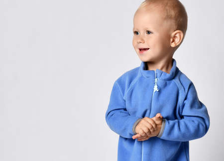 Portrait of happy smiling baby boy in blue fleece jumpsuit stands clapping hands looking at free copy space