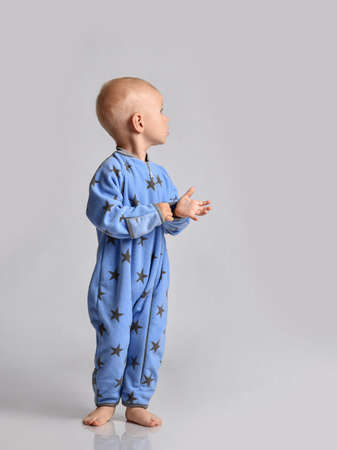 Barefooted baby boy toddler in blue fleece jumpsuit with stars stands side to camera looking back at upper corner Stok Fotoğraf