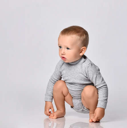 Toddler one-year-old baby boy in diaper and grey one-piece bodysuit with long sleeves sits squatted touching his feet looks aside with interest. Happy infancy and babyhood concept