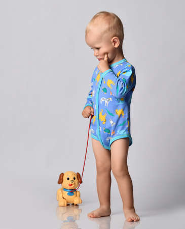Toddler one-year-old baby boy in diaper and blue one-piece bodysuit romper with long sleeves stands with toy dog holding finger at cheek looking down thinking