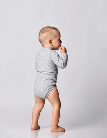 Toddler one-year-old baby boy in grey one-piece bodysuit with long sleeves stand back to camera looking aside holding hand at his mouth. Happy infancy and babyhood concept