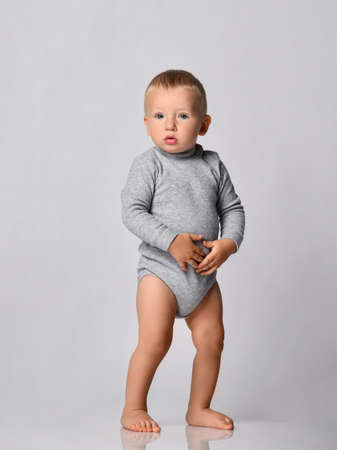 Toddler one-year-old baby boy in grey one-piece bodysuit with long sleeves stands looking at camera holding hands at his stomach. Happy infancy and babyhood concept Stok Fotoğraf
