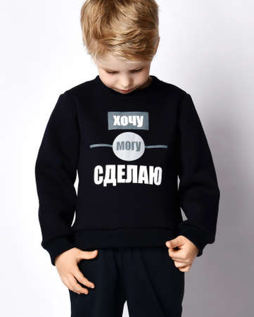 Closeup of blond kid boy in black jersey sweater reading printed words inscription on it  over gray background. Translation:
