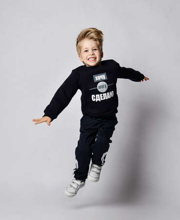 Active frolic blond kid boy in black jersey sweater with printed words inscription on it jumps high over gray background. Translation: