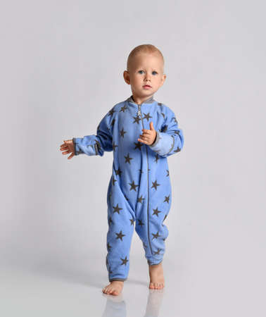 Barefooted baby boy toddler in blue fleece jumpsuit with stars runs walks looking at camera