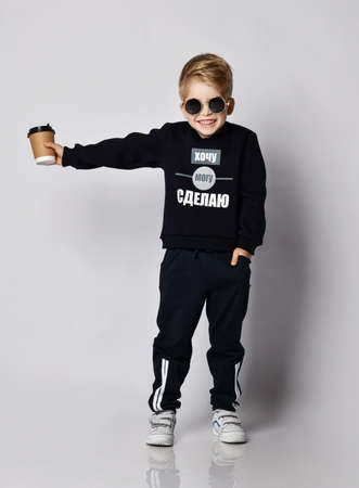 Frolic laughing blond kid boy in sunglasses, black sweater with printed words inscription holds out a cup of coffee tea drink. Translation:
