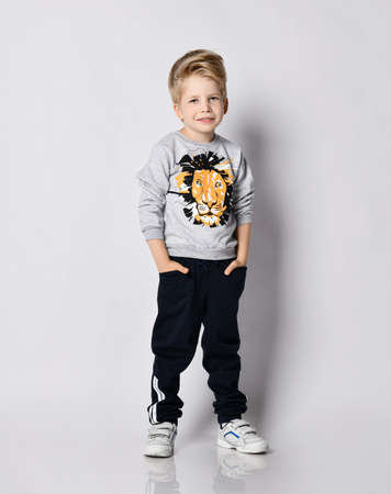 Calm and peaceful blond kid boy in black pants and sweatshirt with lion print stands holding hands in pockets over gray background Stok Fotoğraf