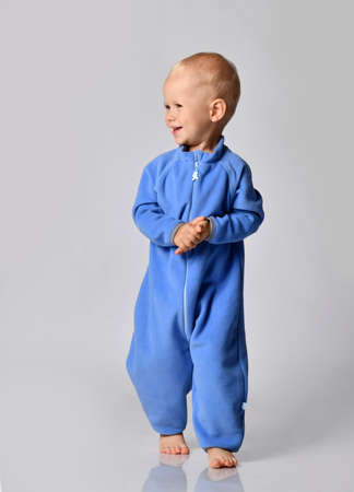 Joyful happy smiling barefooted baby boy in blue fleece jumpsuit stands clapping hands looking at free copy space