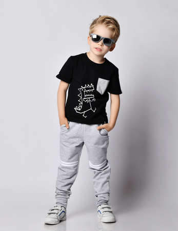 Cool blond kid boy in sunglasses, black t-shirt with dinosaur print and gray pants stands leaning sideways holding hands in pockets over gray background
