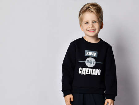Portrait of self-confident cheerful blond kid boy in black jersey sweater with printed words inscription on it  over gray background with copy space. Translation: