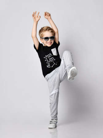 Playful frolic blond kid boy in sunglasses, black t-shirt with dinosaur print and gray pants stands holding hands and foot up over gray background