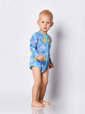 Toddler one-year-old baby boy in diaper and blue one-piece bodysuit romper with long sleeves and animals print stands side looking at camera Stok Fotoğraf