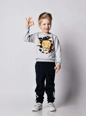 Frolic cheerful blond kid boy in black pants and sweatshirt with lion print gestures shows OK sign over gray background