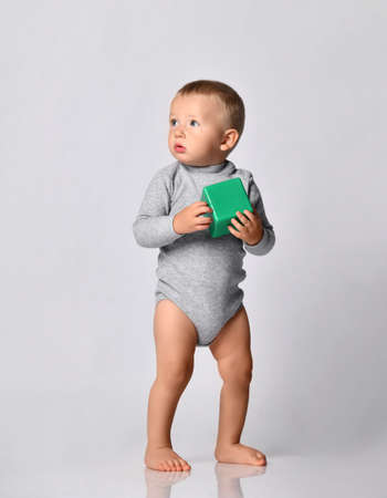 Toddler one-year-old baby boy in diaper and grey one-piece bodysuit with long sleeves stands holding green toy block looking at upper corner. Happy infancy and babyhood concept