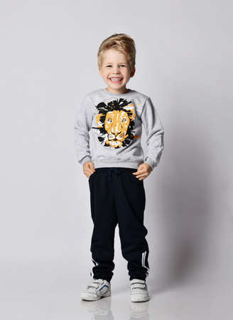 Frolic cheerful blond kid boy in black pants and sweatshirt with lion print giggles holding hands in pockets over gray background Stok Fotoğraf
