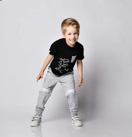 Playful frolic blond kid boy in sunglasses, black t-shirt with dinosaur print and gray pants stands leaning forwards going to run out playing catch-up over gray background Stok Fotoğraf