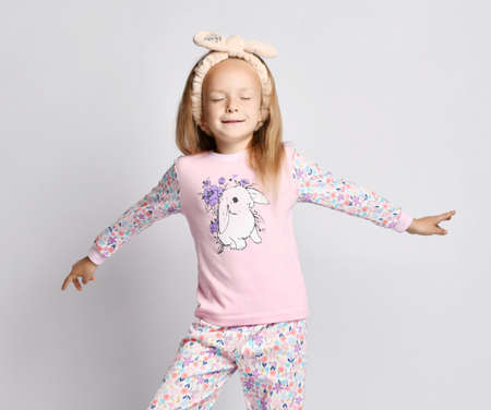 Blonde kid girl in headband, stylish suit shirt and pants with flower print pattern and rabbit, pajamas stands with her arms spread wide and eyes closed over gray background