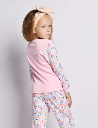 Blonde kid girl in headband, stylish pink shirt and pants with flower print pattern stands back head turned looking at camera over her shoulder