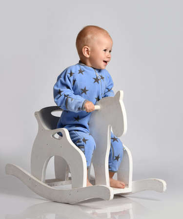 Happy screaming barefooted baby boy in blue fleece jumpsuit with stars plays has fun riding white kids rocking horse toy swinging and looking aside