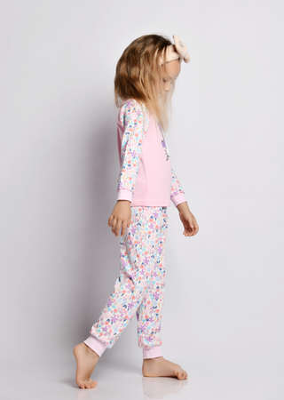 Sleepy sad blonde kid girl in headband, stylish shirt and pants pyjamas with flower print pattern walks looking down over gray background. Side view