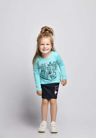 Playful frolic smiling blonde kid girl in stylish shirt and denim skirt with cats kitties and sneakers stands leaning forward looking peering at camera over gray background