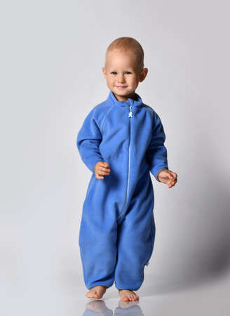 Barefooted happy baby boy toddler in blue fleece jumpsuit with zipper runs walks looking at camera