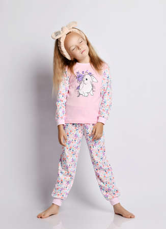 Sleepy barefooted blonde kid girl in headband, stylish shirt and pants pyjamas with flower print pattern stands with her eyes closed and head tilted over gray background Stok Fotoğraf