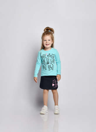 Frolic smiling blonde kid girl in stylish shirt and denim skirt with cats kitties and sneakers walks looking at camera over gray background. Front view Stok Fotoğraf