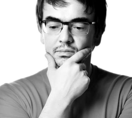 Black and white portrait of man in glasses touching chin and thinking over white background, close-up. Expressing emotions and moods concept